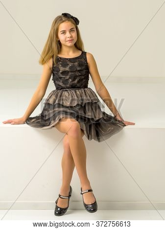 Beautiful Girl Sitting On Ledge Of The Wall And Smiling At Camera, Portrait Of Pretty Blonde Teenage