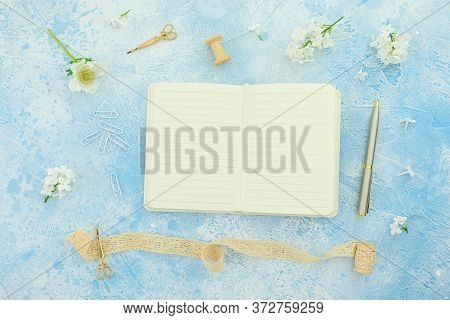 Summer Composition Of Flowers With White Diary, Tassel, Scissors And Pen On Blue Background. Flat La
