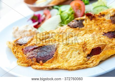 Omelet with spinach, mushrooms and chorizo cooked in old vintage pan served with three slices of bread