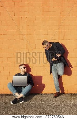 Two Friends In Casual-wear In Urban Contest With Digital Devices. Young Caucasian Man Sitting Cross-