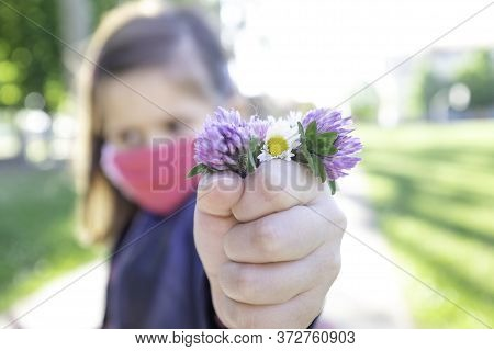Little Cute Girl With Protective Mask Holding Bunch Of Wildflowers -  Close Up View On The Hand With