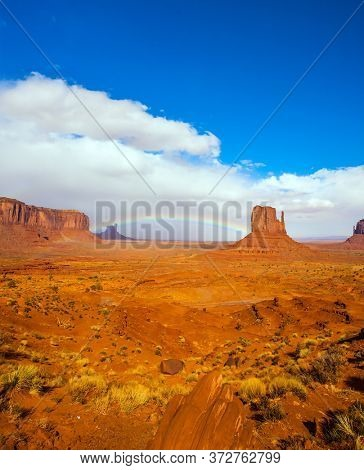 The USA. Magnificent rainbow across the sky. Monument Valley is geological formation. Huge masses of red sandstone - outliers on the Navajo Indian Reservation. Concept of photo tourism