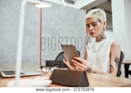 Young Stylish Blonde Tattooed Business Woman Using Touchpad While Sitting At Her Working Place In Th