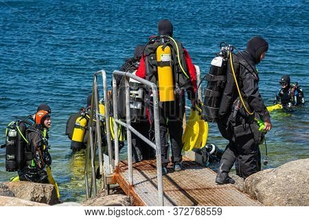 Malmö, Sweden - June 14, 2020: Scuba Divers Enters The Water For A Scuba Dive In The Ocean