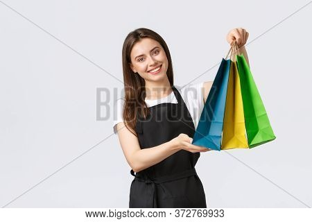 Friendly-looking Nice Female Cashier Smiling Pleasant And Handing Over Bags With Purchased Items To