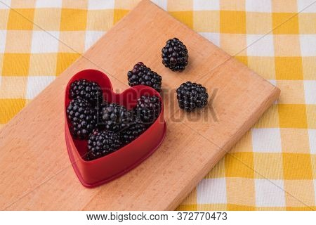 Heart-shaped Form Filled With Natural Fresh Ripe Blackberries. Berries Love Concept. Wooden Kitchen