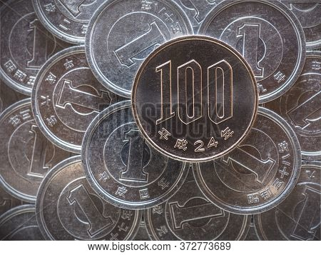 100 One Hundred Yen Lie On A Field Of Japanese Coins At 1 Yen. News About The Economy, Finance And I