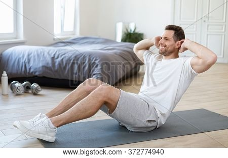 Stay Fit Concept. Man Exercising Doing Abs Sit-ups Sitting On Gymnastics Mat Training At Home.
