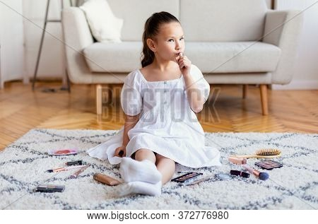 Beautiful Kid Girl Making Makeup Putting On Lipstick Playing With Cosmetics Sitting On Floor At Home