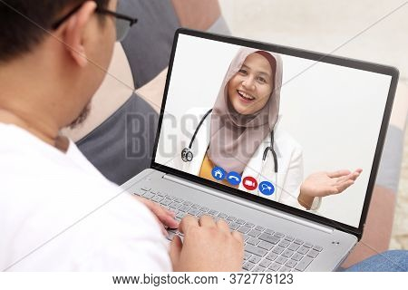 Concept Of Online Medical Healthcare Services, Shows Laptop Display With Asian Muslim Female Doctor
