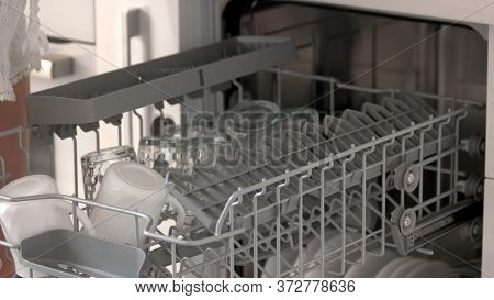 Close Up Open Dishwasher With Clean Cups. Dishwasher At Home Kitchen. Cleaning Chores Concept.