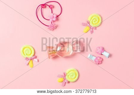 Childrens Flat Lay. Perfume In The Form Of Candy, Childrens Jewelry And Hair Accessories On A Pink B