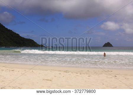 Female Tourist In Bathing Suit Enters Sea At Mawun Beach, Lombok. Kuta Lombok Is An Exotic Paradise