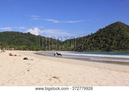 Man And Horse On White Sand Beach, Mawun, Lombok. Kuta Lombok Is An Exotic Paradise On The Indonesia