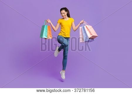 Seasonal Sales. Happy Young Asian Girl Jumping In Air With Lots Of Shopping Bags In Hands Over Purpl