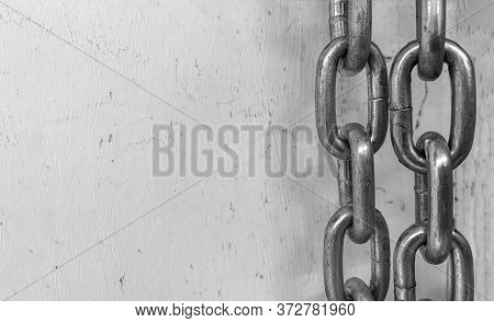 Large Chain Links On A Gray Background. The Concept Of Bondage And Restriction Of Freedom. Slavery.