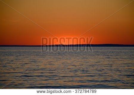 Bright Sunset Over The Lake. Red-orange Sunset. Dark Water. The Sun Has Set Over The Horizon.