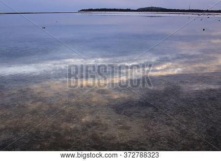 Cloudy Sky Reflected In Calm Water At Low Tide Before Dusk And Gili Meno Island Silhouette In The Di