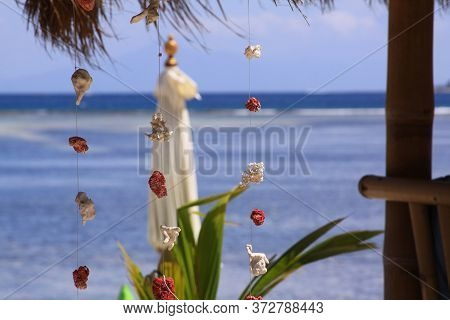Red And White Coral Pieces Decorations Design, Hanging On Wire At Exotic Beach Bar, With Blurred Umb