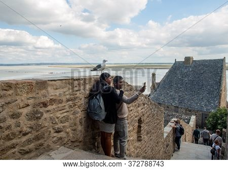 Le Mont-saint-michel, France - September 13, 2018: A Pair Of Hindus Take A Picture With A Seagull In