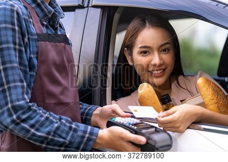 Portrait of asian woman make mobile payment contactless technology for online grocery ordering and drive thru service. Drive through and food online is new normal popular after coronavirus pandemic.