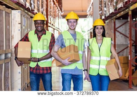Portrait of caucasian white and african black warehouse workers hold cardboard box packaging in warehouse distribution center environment. Using in business warehouse diversity and logistic concept.