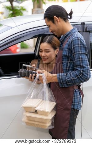 Asian woman customer make mobile payment contactless technology on drive thru food service restaurant while picking up. Drive through is new normal more popular after coronavirus covid-19 pandemic.