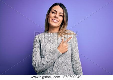 Young beautiful woman wearing casual sweater standing over isolated purple background cheerful with a smile of face pointing with hand and finger up to the side with happy and natural expression