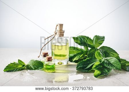 Peppermint Essential Oil And Fresh Mint Leaves On A Light Background.