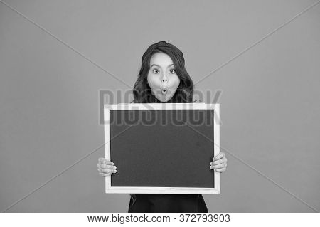 Uncovering Surprising Information. Surprised Girl Hold Blank Blackboard For Information. Small Child