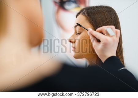 Cosmetician puts makeup on a woman's face