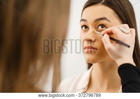 Cosmetician applies makeup on a woman's face