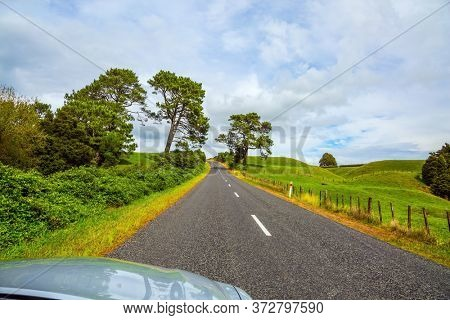 Way to Rotorua. Fabulous faraway country. Road among the green fields of the North Island of New Zealand. Car tourism concept