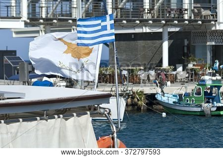 Cypriot And Greek National Flags Waving On A Boat Moored At Sea Harbor