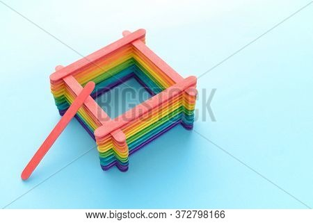 Creative Construction Made Of Colorful Wooden Sticks In Rainbow Colors With One Stick Left Outside.