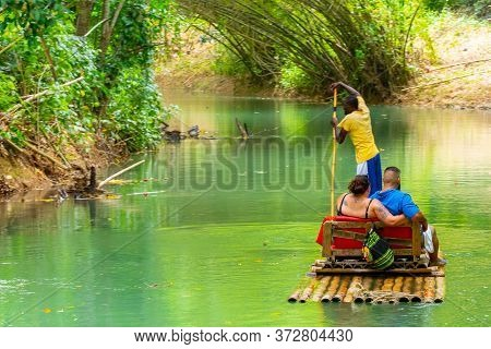 Falmouth, Jamaica - July 07 2019: Martha Brae River, Jamaica. Tourists On Bamboo Raft Rides. Relaxin