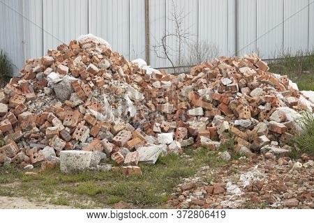 A Pile Of Used Red Bricks In The Yard.