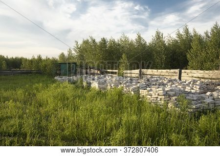 A Pile Of New White Bricks In The Yard With Green Grass And Near Forest. Concept Of Building New Cou