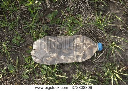 Old Plastic Damaged And Dirty Bottle In The Park. Nature Pollution Concept