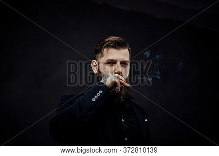 Elegantly Dressed Bearded Male With Tattoos On His Neck And Hand Lights A Cigar. Brutal Young Busine