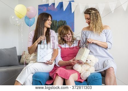 Three Women Opening Presents In The Baby Shower Party. They Are Happy And Smiling, As They Open And