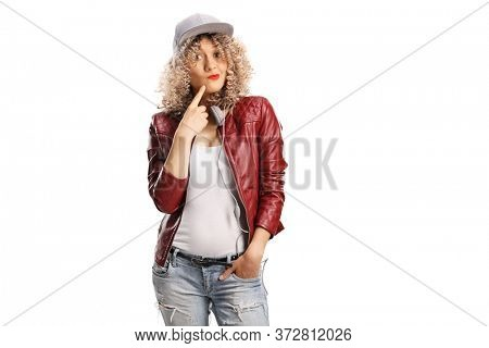 Young woman with a curly blond hair and a cap wearing a red leather jacket with an ignorant expression isolated on white background
