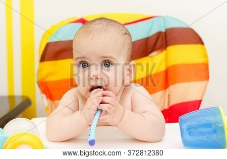 Little Toddler Baby Boy Eating By Himself. Small Child Holding Plastic Spoon And Eat Baby Food. Conc