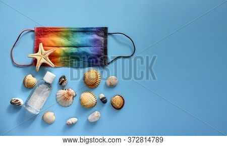 Summer vacation 2020 flat lay with protective mask painted in rainbow colors, antiseptic, pebbles, s