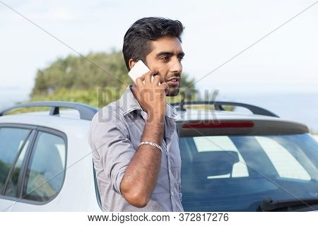Man Talking On A Cell Phone Leaning On The Door Of His Car Having A Conversation