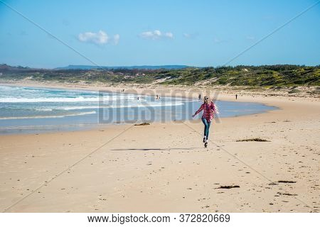A Girl Skipping On A Scenic Beauriful Sandy Bendalong Beach On Sunny Winter Day. Bendalong, Nsw, Aus