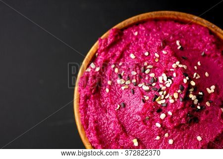 Top view and close up of a colorful beetroot hummus with spoon on a black background