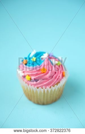 Cupcakes with blue and pink icing on a blue background