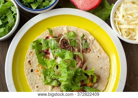 Yellow plate mexican beef tacos with condiment tomato, lettuce, coriander, cheese on a wooden table