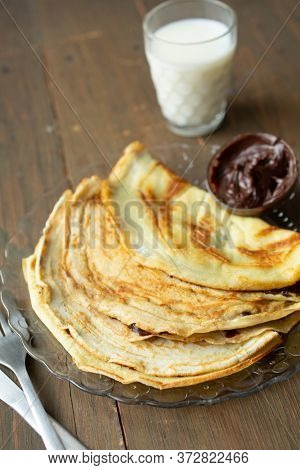Three pancakes fill with chocolate and a glass of milk on a wooden background